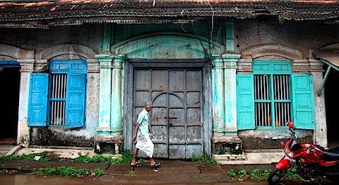 Man walking past decaying building